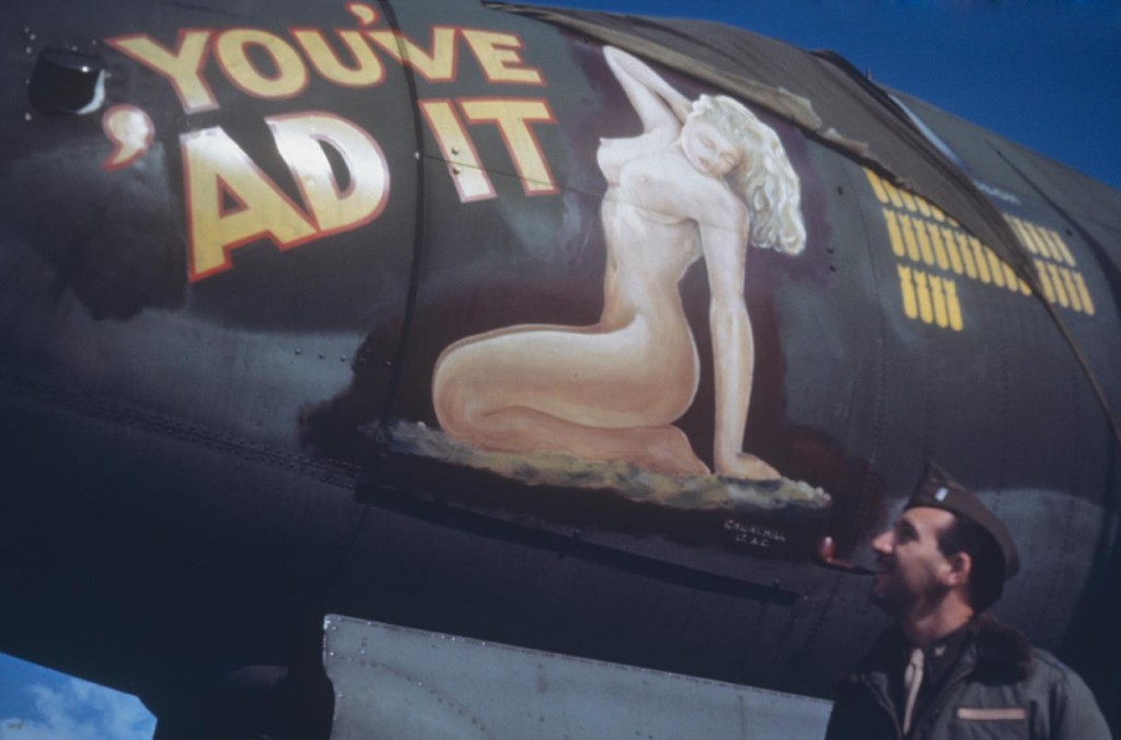 "Lieutenant Jack Havener of the 344th Bomb Group admires a pin up nose art of a B-26 Marauder (serial number 42-95952) nicknamed ""You've 'Ad It"". Stansted. July 1944."